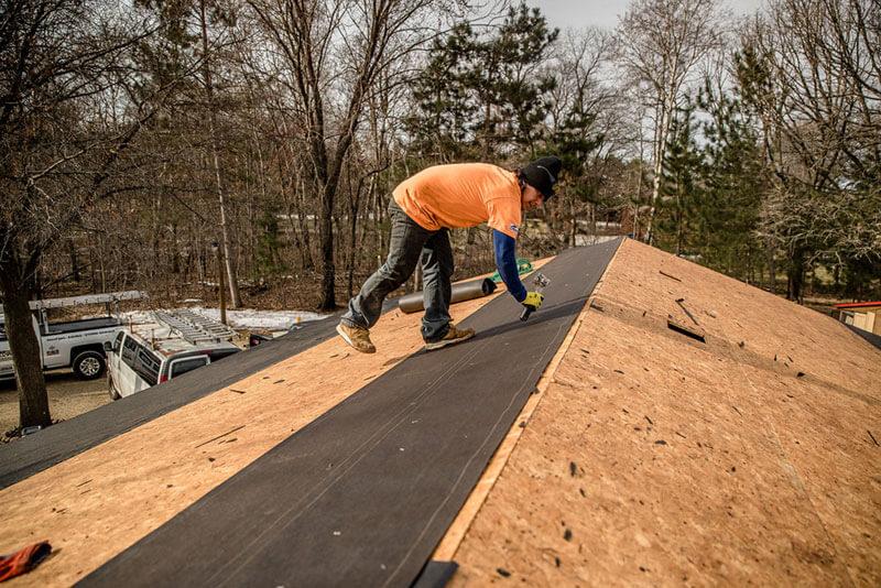 man using staple hammer to install roof felt