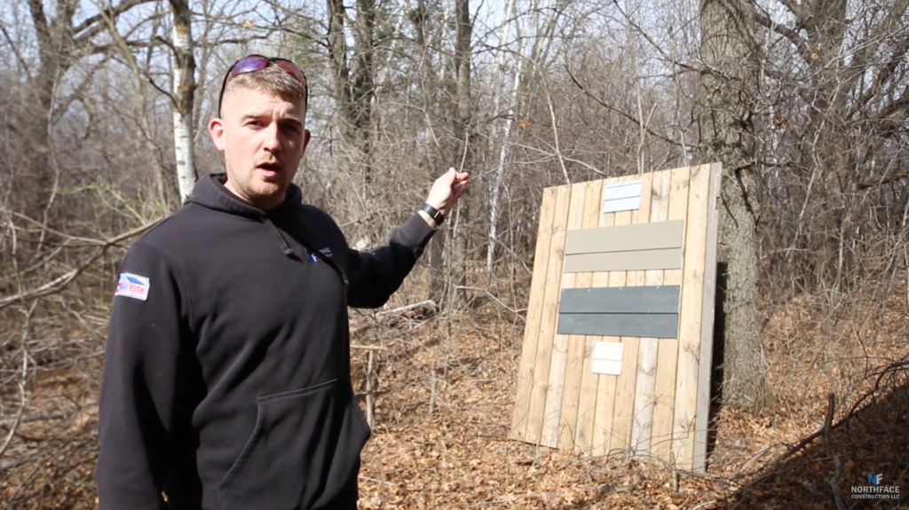 Man pointing at wood panel board in woods