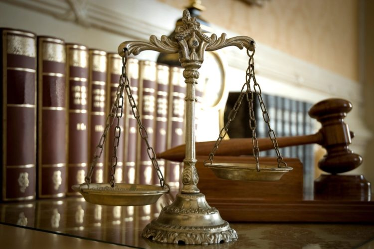 Scales of justice on a desk with gavel and law books in the background.