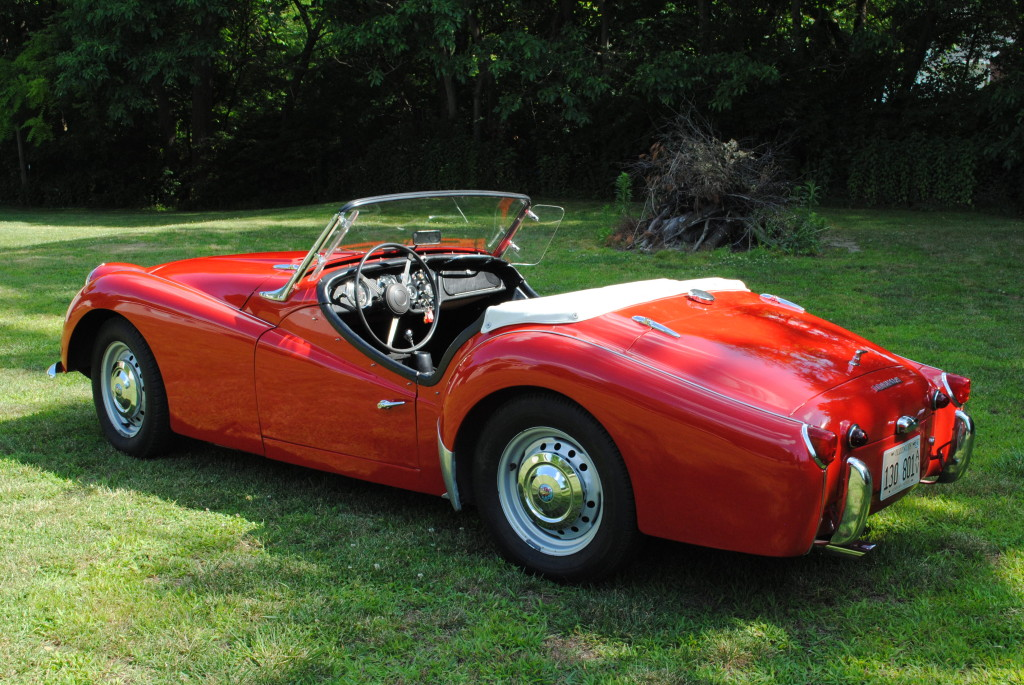 """Brian and Jane Kinney-Our car is a 1961 Triumph TR3A. It was first imported and purchased in Kansas City Mo. It was then shipped to Hawaii by the original owner where it was purchased by my father in 1963 for my mother on her birthday. My father was a USAF pilot so the car was moved and shipped several times in the first 20 years of its life. It was placed in storage for 7 years while we were stationed overseas. In 1975 I learned to drive in Moms """"little red car"""" and in 1976 I took my 1st driving test in it. I drove the car during my junior and senior years in high school. In 1979 my father retired and took the car to South Carolina. Eight years ago my parents were in the process of downsizing and I became the steward of the family car. It received a re-spray about 15 years ago, other than that, just maintenance. Owning the TR has been a privilege and a learning experience. My favorite day with the car is when my youngest daughter used it in her wedding. Many people ask, """"How do you fit in there?"""" My reply is always the same: Perfectly."""
