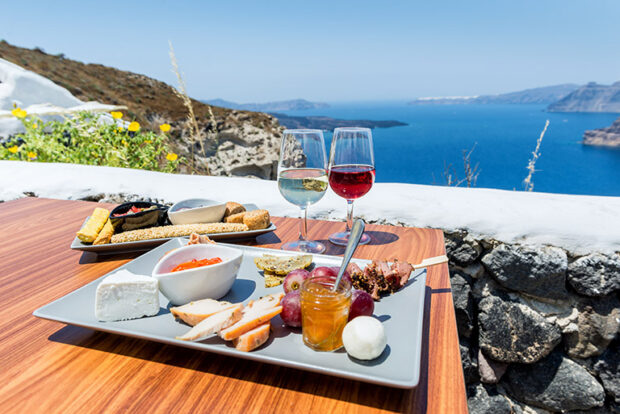 Wine and charcuterie on a table overlooking the water in Greece