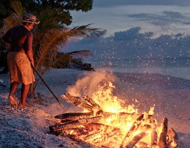 A man stoking a fire on the beach. Rangiroa. Credit: Hélène Havard / Tahiti Tourisme