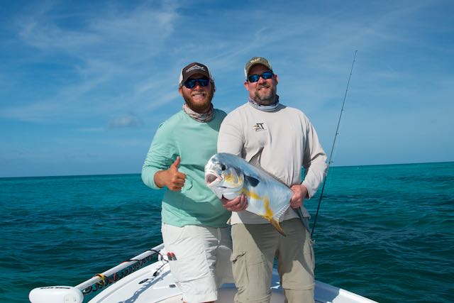 Capt. Kyle Kelso with a happy customer and his permit