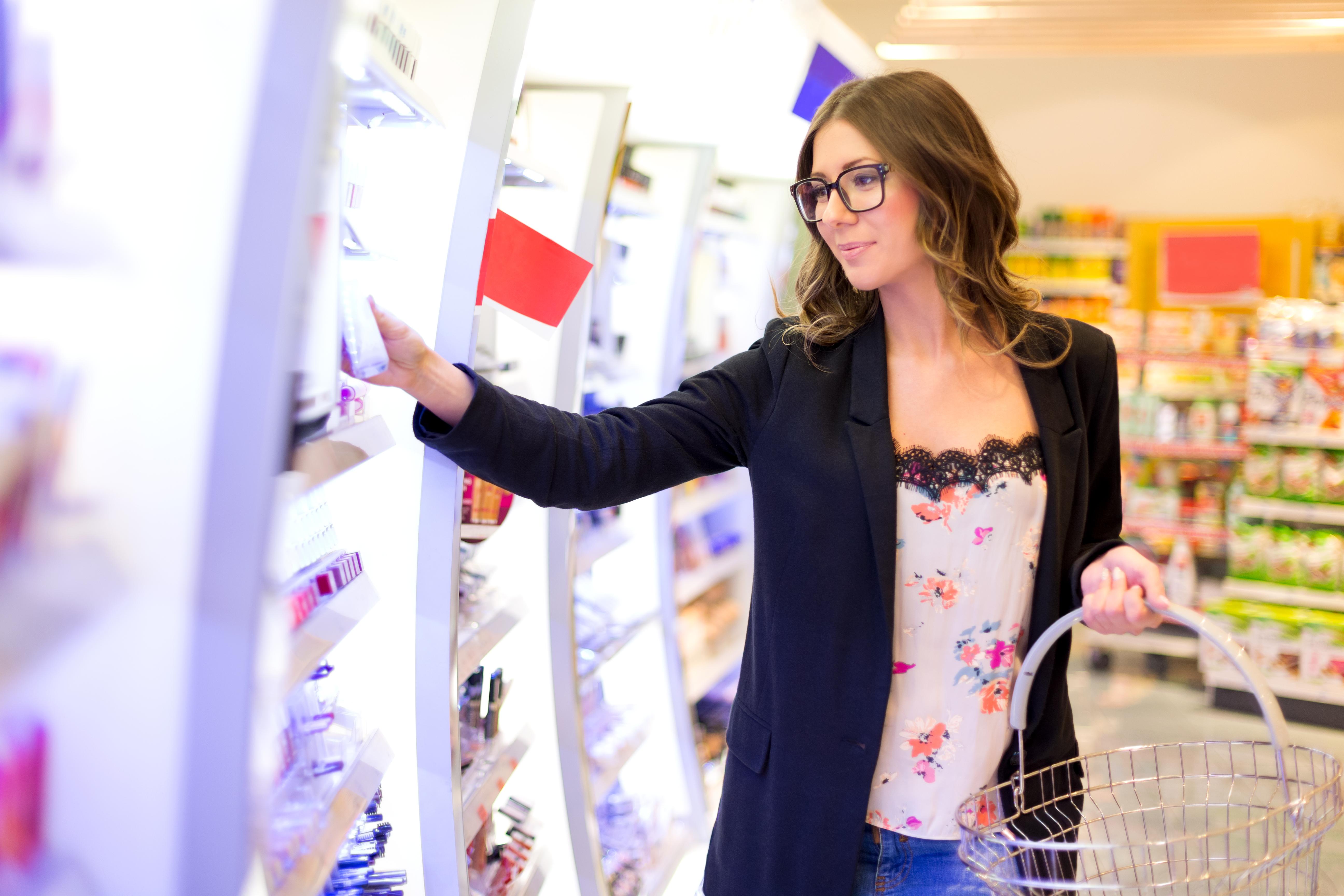 Beautiful woman choosing perfect beauty product in shopping mall, looking through shelfs, copy space