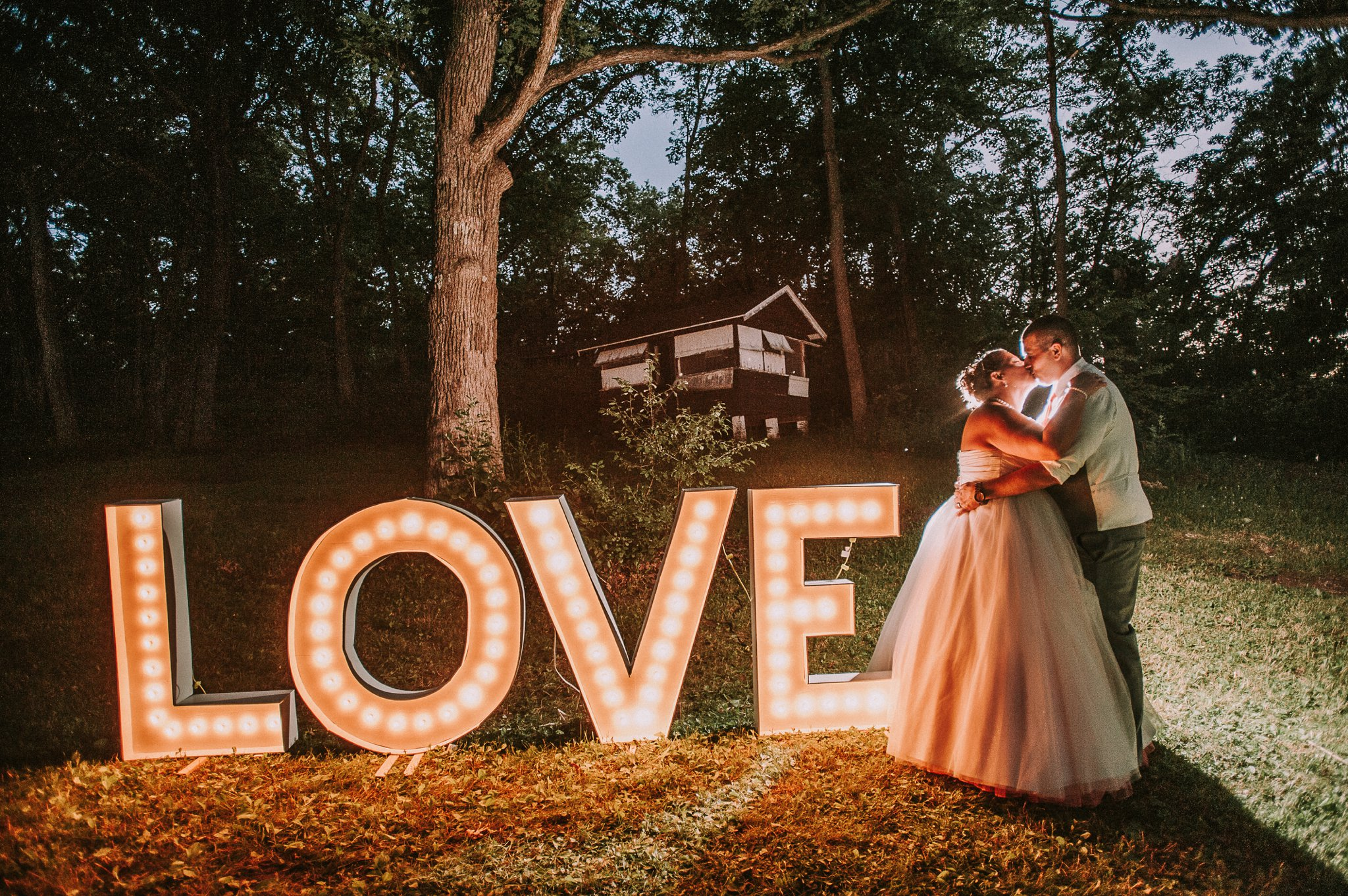 DIY wedding couple standing near their homemade sign.