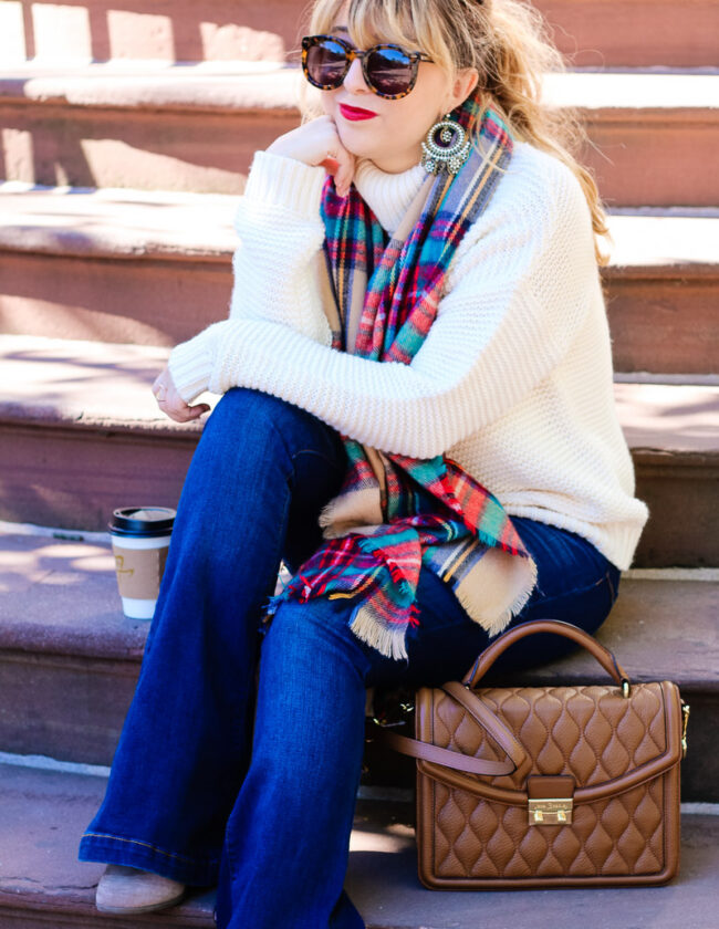 Fall outfit idea: turtleneck sweater, flare jeans and plaid blanket scarf