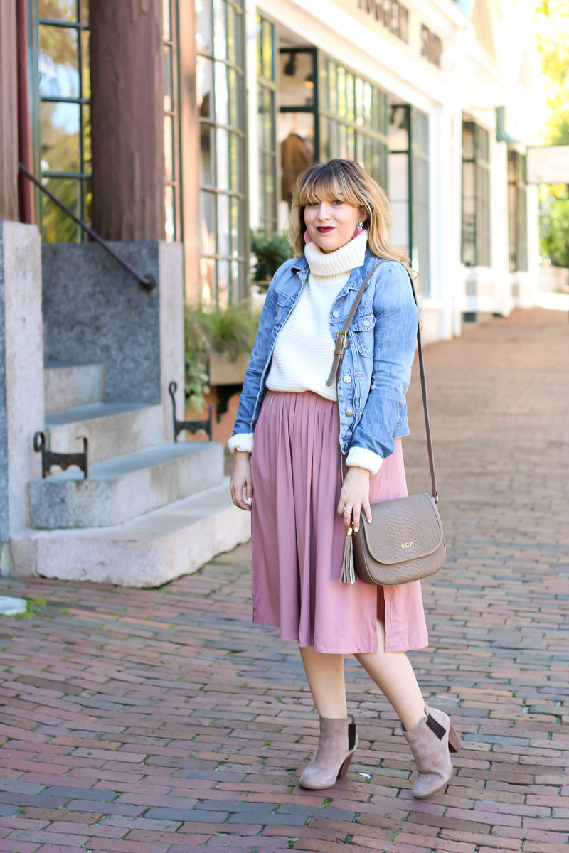 Miami fashion blogger Stephanie Pernas styles a pink midi skirt with a turtleneck sweater and jean jacket for a cute fall outfit idea.