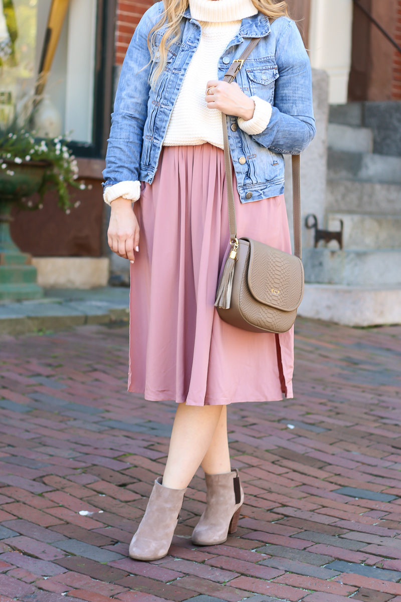 Miami fashion blogger Stephanie Pernas styles light fall layers by pairing a midi skirt with a turtleneck sweater and jean jacket.