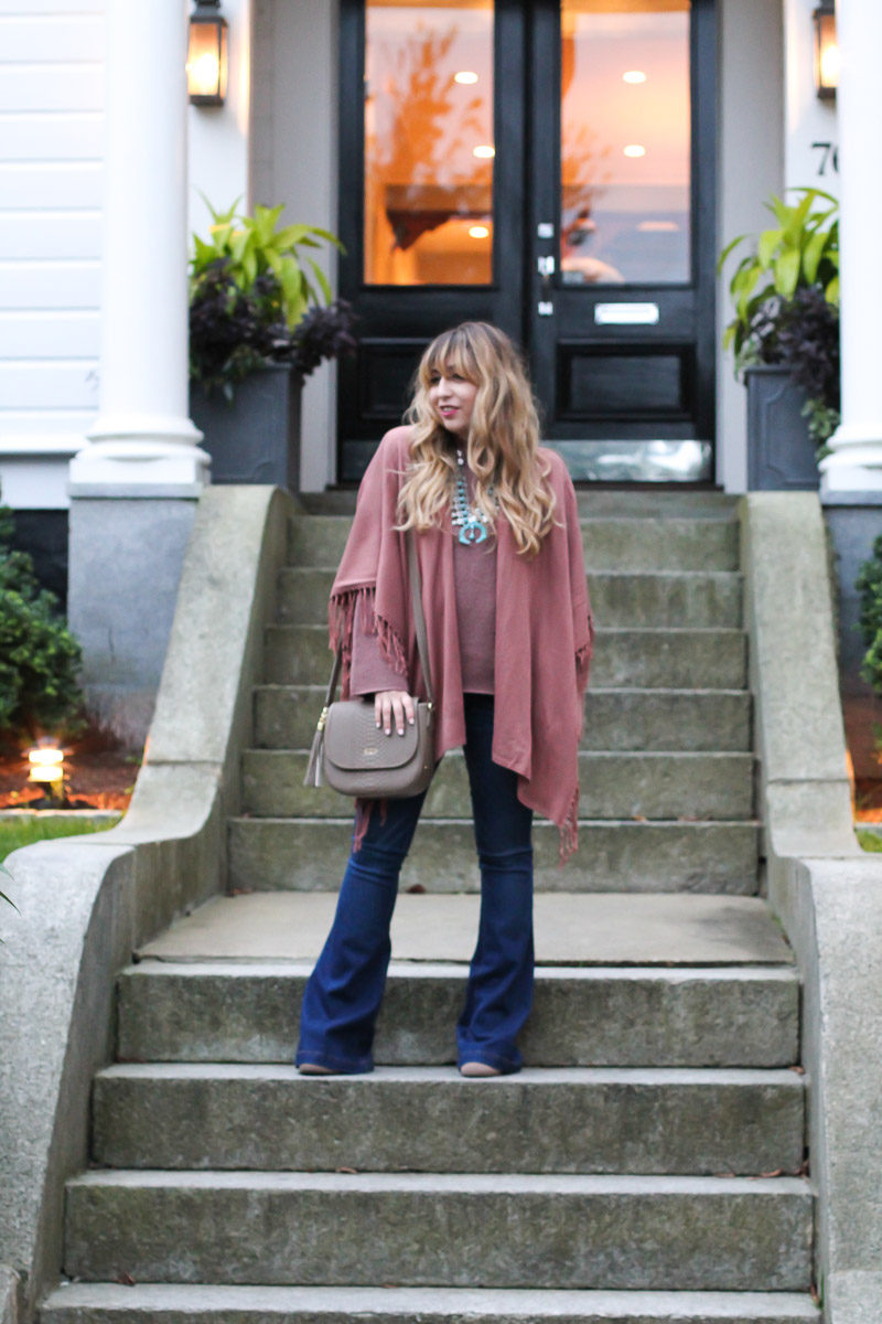 Miami fashion blogger Stephanie Pernas wears flare jeans, a fringe poncho and a bell sleeve sweater
