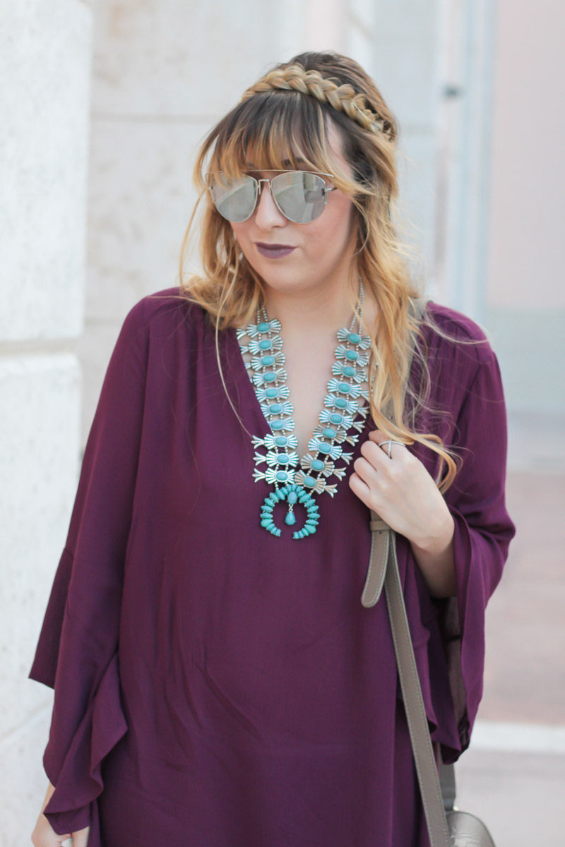 Fashion blogger Stephanie Pernas wearing a plum bell sleeve dress and braided hairstyle
