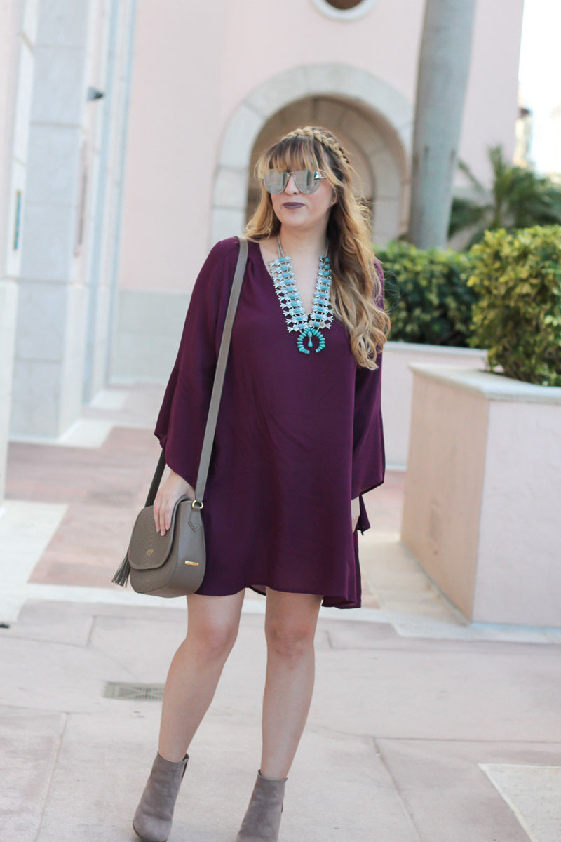 Miami fashion blogger Stephanie Pernas wearing a plum dress with turquoise statement necklace for a comfy Thanksgiving dress idea