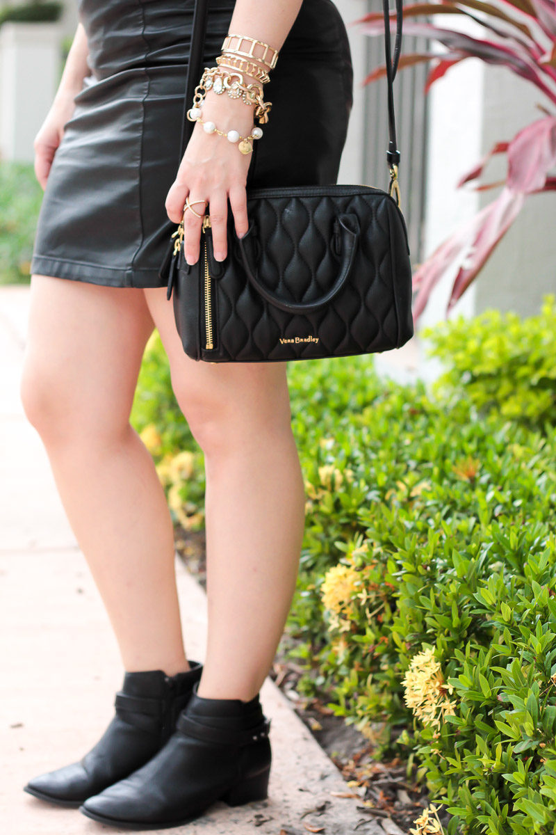 Miami fashion blogger Stephanie Pernas wearing a Vera Bradley Mini Marlo bag with ankle boots and a leather skirt