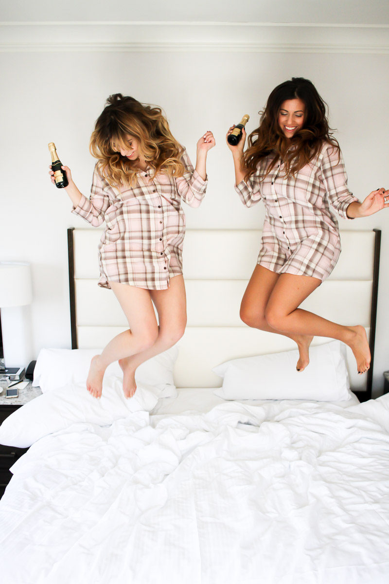 Fashion bloggers Stephanie Pernas of A Sparkle Factor and Jaime Cittadino of Sunflowers and Stilettos jump on the bed in PJ Salvage plaid sleepshirts on a girls' trip to Boston