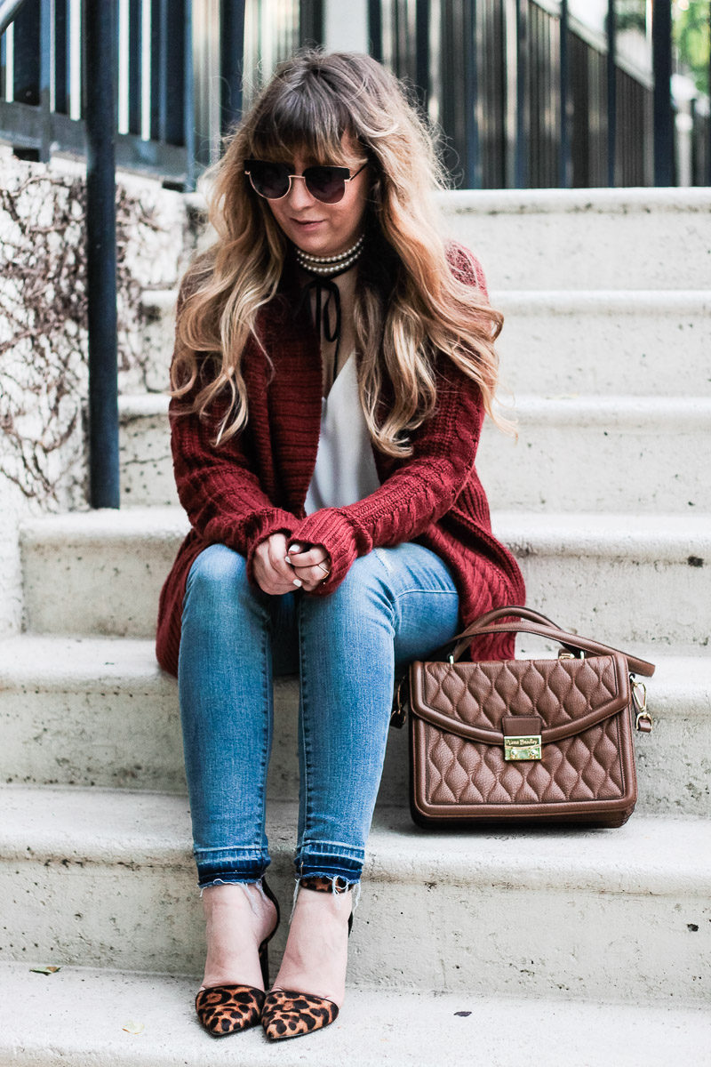 Miami fashion blogger Stephanie Pernas of A Sparkle Factor styles a cable knit cardigan with jeans and the Vera Bradley Lydia satchel in cognac