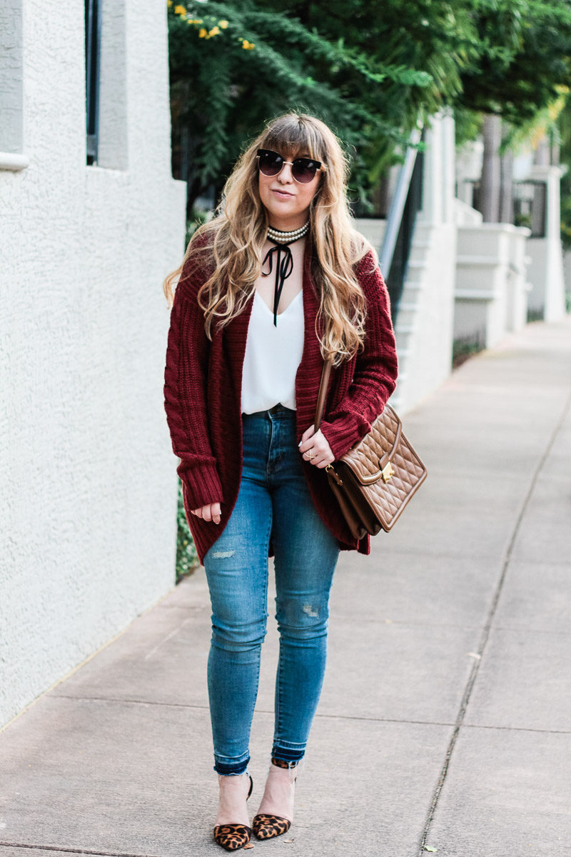 Miami fashion blogger Stephanie Pernas of A Sparkle Factor wearing a burgundy cardigan with jeans and leopard pumps