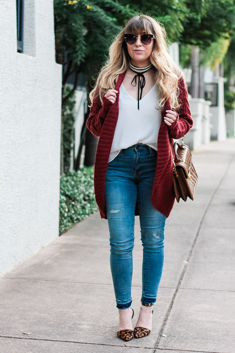 Miami fashion blogger Stephanie Pernas of A Sparkle Factor styles a cable knit cardigan with a pearl choker and high waist jeans for a chic fall outfit idea