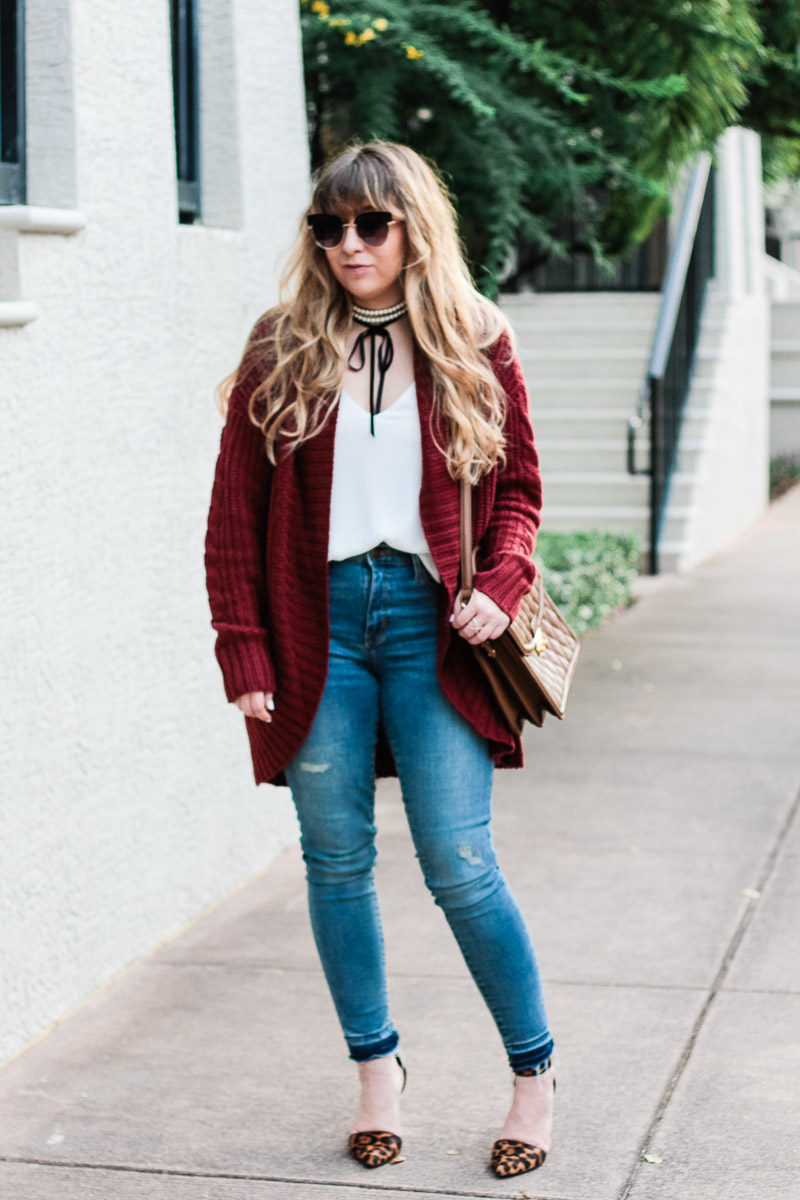 Miami fashion blogger Stephanie Pernas of A Sparkle Factor styles a burgundy cardigan with jeans and leopard pumps for a casual fall outfit idea