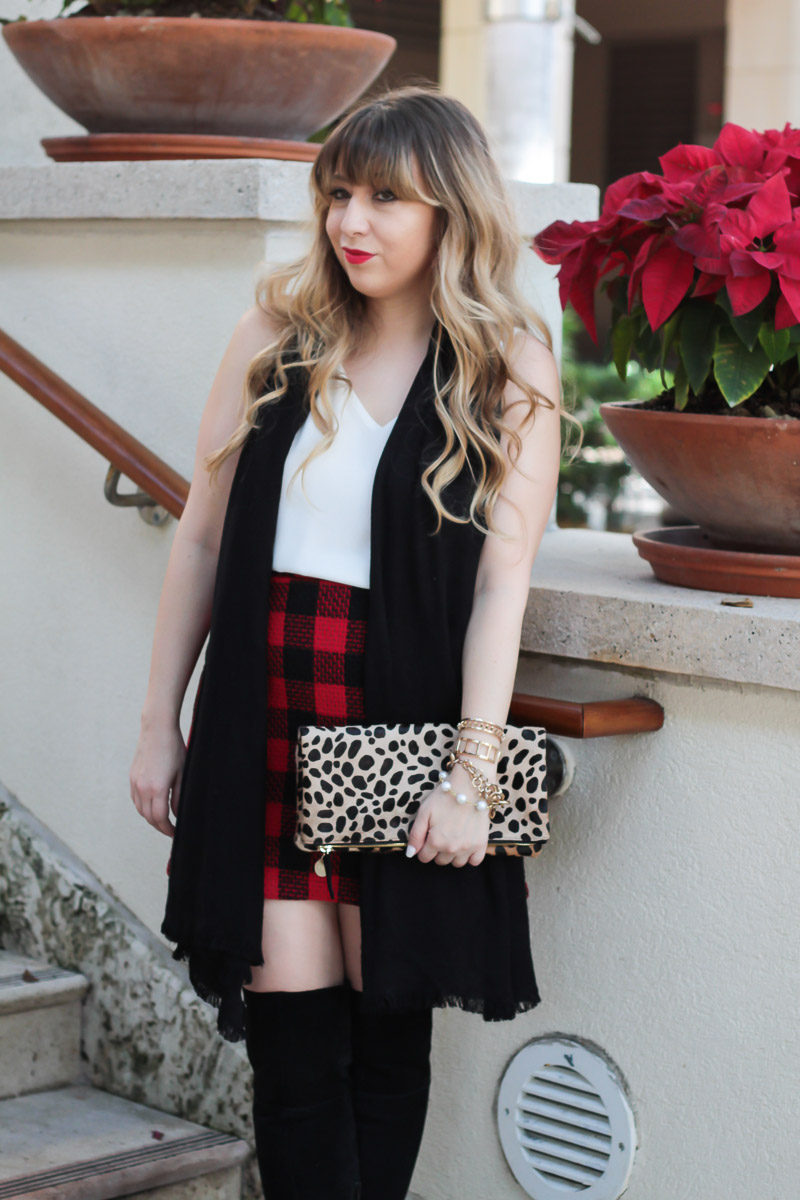 Fashion blogger Stephanie Pernas styles a red buffalo plaid skirt with a black scarf and over the knee boots for a Christmas outfit idea