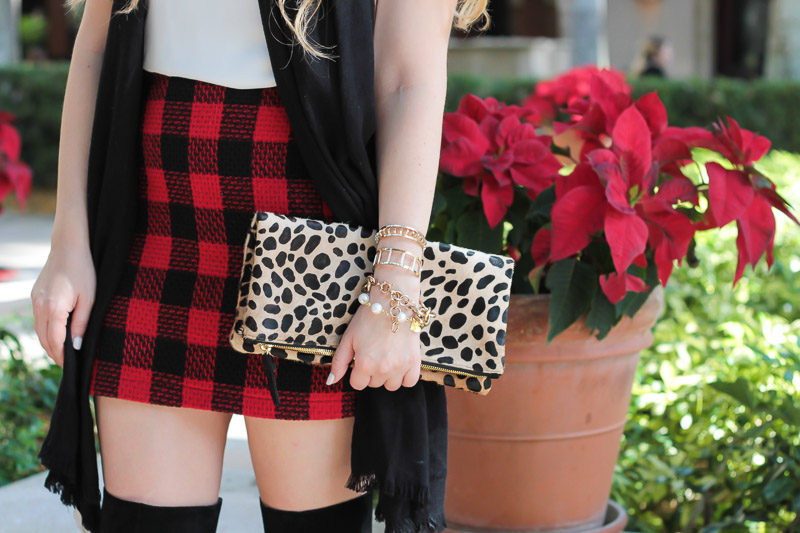 Miami fashion blogger styles a Clare V leopard foldover clutch with a buffalo plaid skirt and over the knee boots for a festive holiday outfit idea