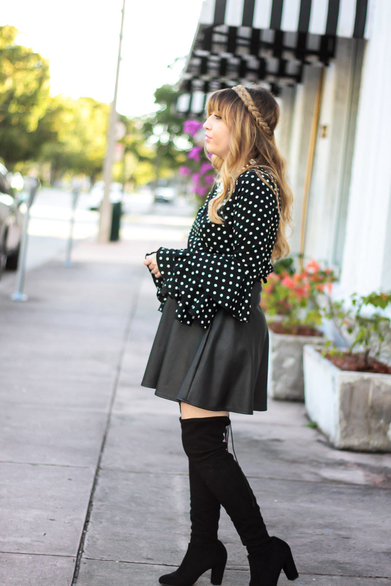 Fashion blogger Stephanie Pernas styles a polka dot blouse with leather skirt and over the knee boots