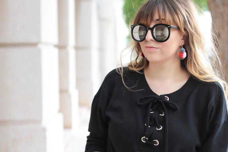 Miami fashion blogger Stephanie Pernas wearing a black lace up sweater and Baublebar pompom hoop earrings
