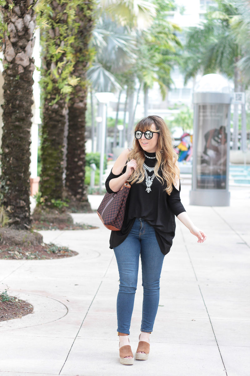 Miami fashion blogger Stephanie Pernas of A Sparkle Factor wearing a Shein cold shoulder top and Baublebar Supernova choker set with jeans and Marc Fisher wedges