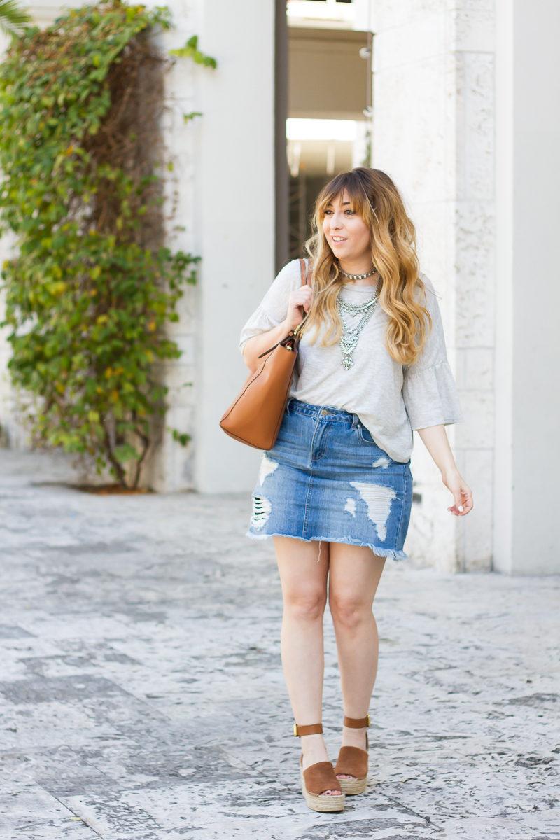 Miami fashion blogger Stephanie Pernas wearing a gray ruffle sleeve t shirt and jean skirt