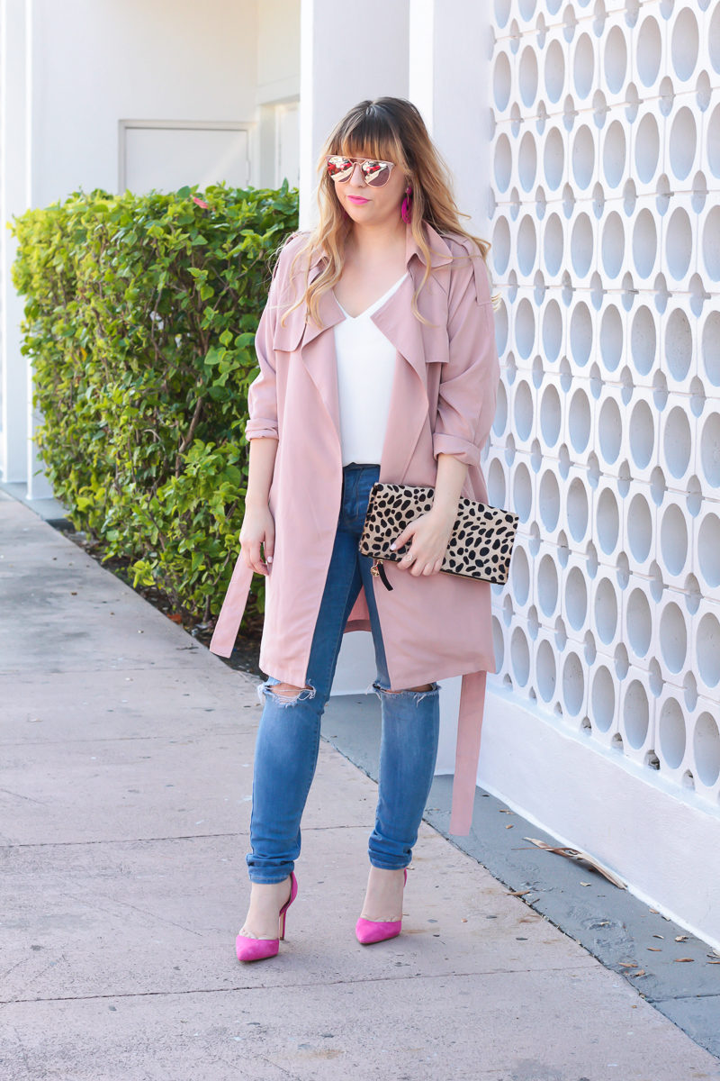Miami fashion blogger Stephanie Pernas of A Sparkle Factor wearing a pink trench coat with jeans for a casual Valentine's Day outfit idea