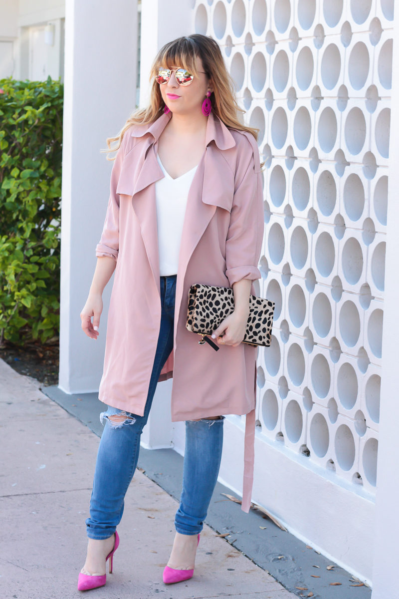 Miami fashion blogger Stephanie Pernas of A Sparkle Factor styles a cute trench coat outfit idea by pairing a pink trench coat with skinny jeans and bold pumps