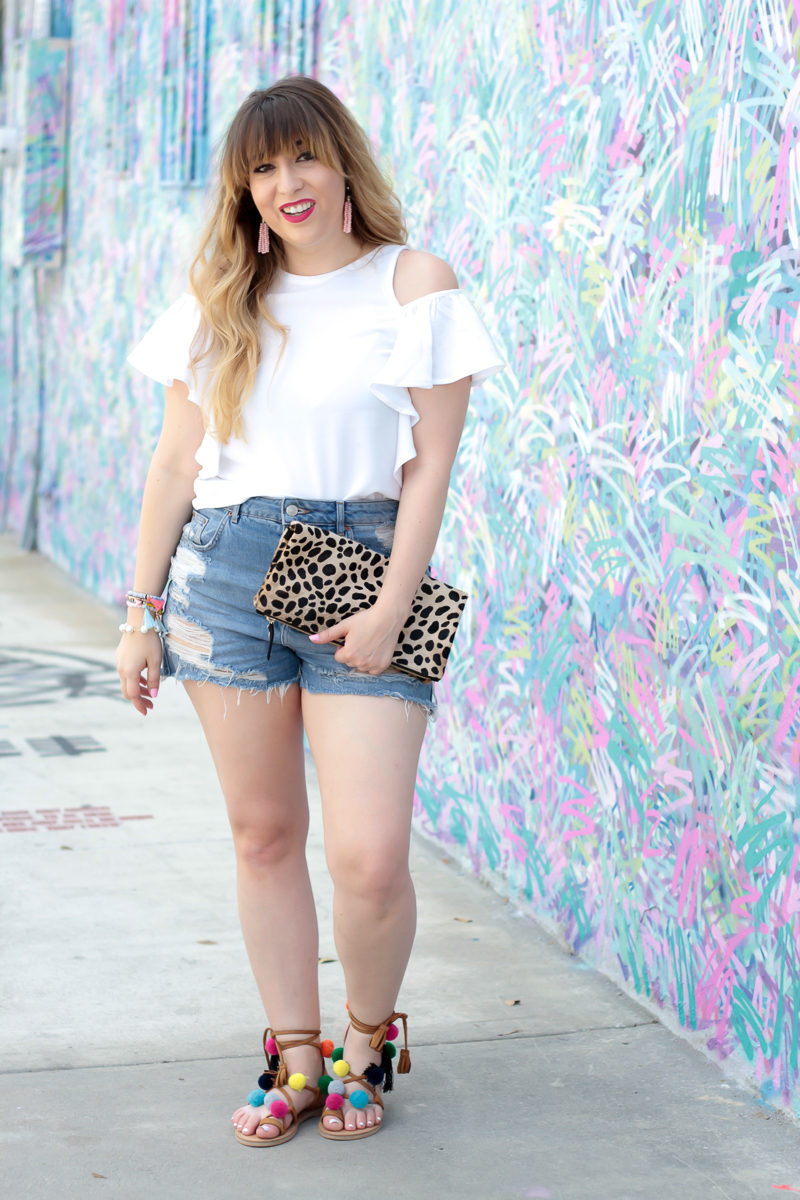Miami fashion blogger Stephanie Pernas wearing Topshop jean shorts and a Lush flutter sleeve top with pom pom sandals