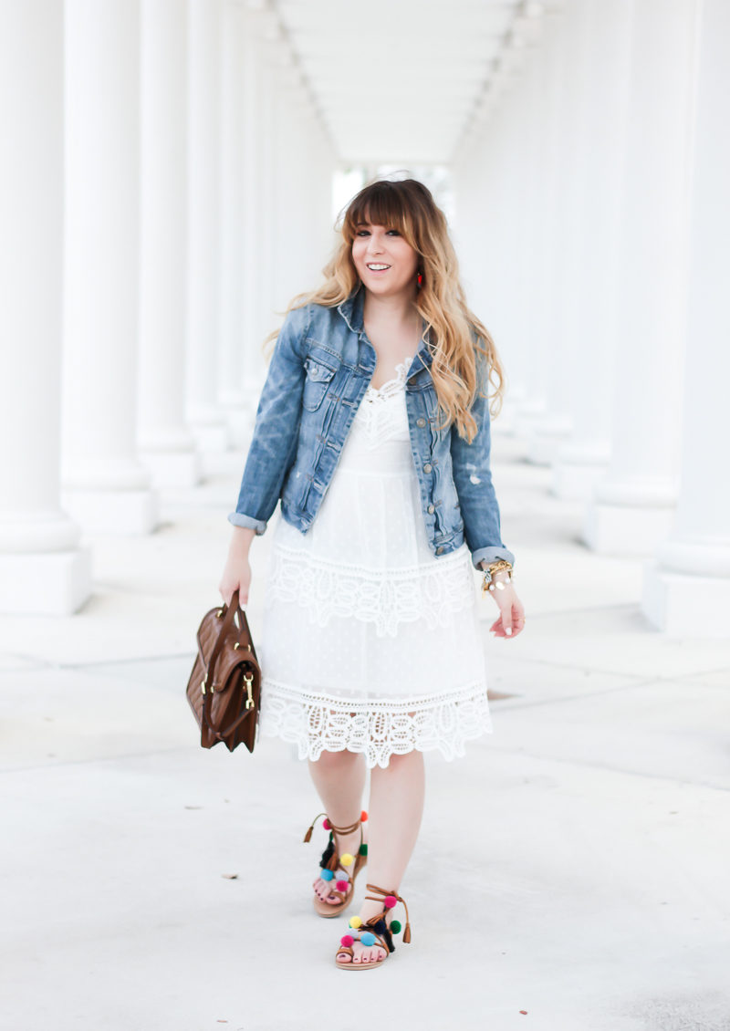 Miami fashion blogger Stephanie Pernas styles a white lace dress with jean jacket and pompom sandals for a cute spring outfit idea