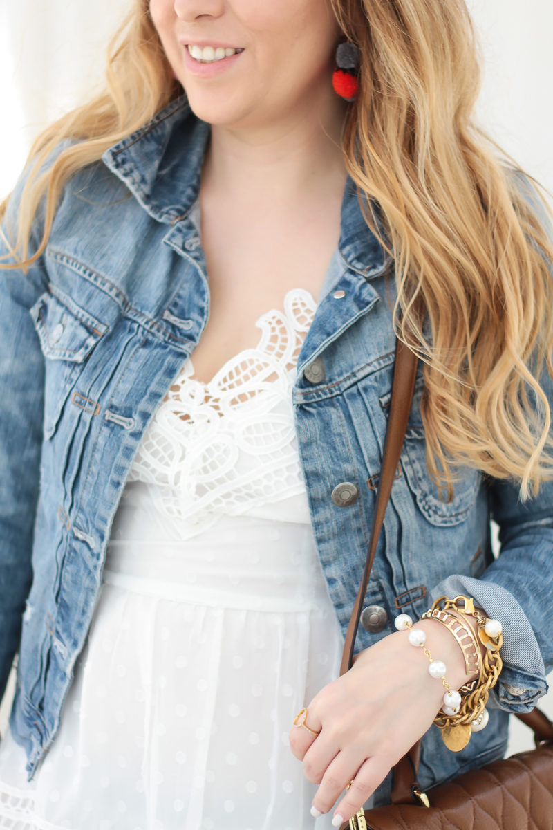 Miami fashion blogger Stephanie Pernas wearing a white lace dress with a jean jacket for a feminine spring outfit idea