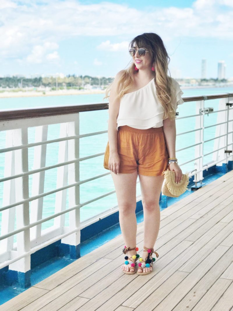 Miami fashion blogger Stephanie Pernas wearing a one shoulder ruffle top and shorts with pom pom sandals