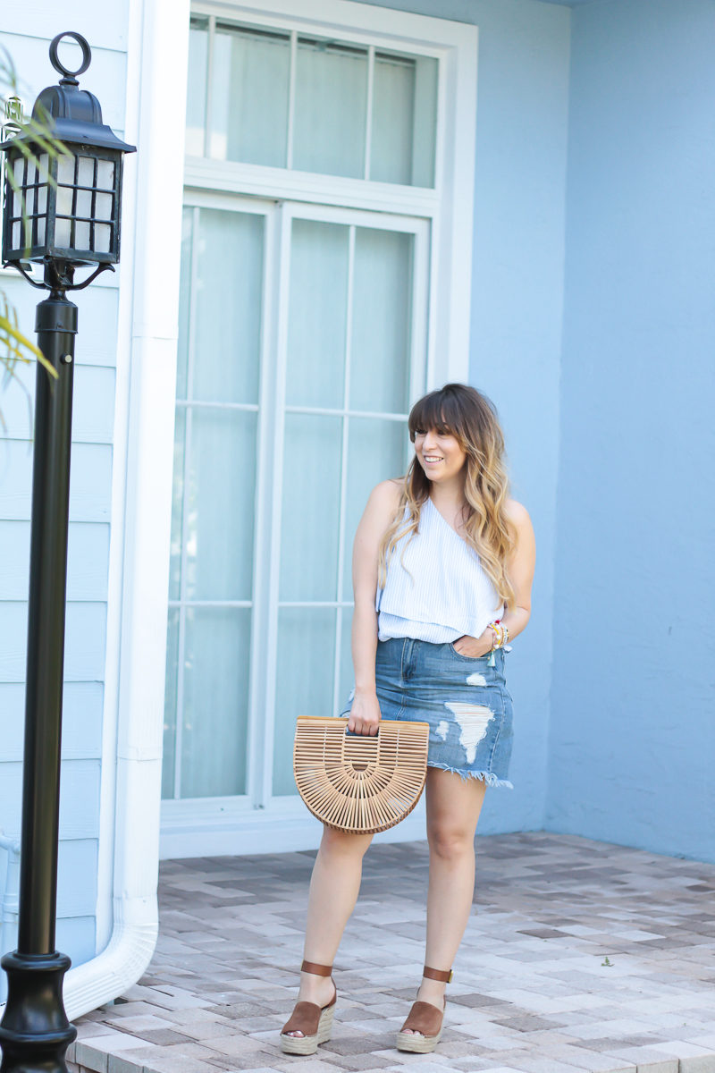 Miami fashion blogger Stephanie Pernas wearing a blue stripe one shoulder top and jean skirt for spring