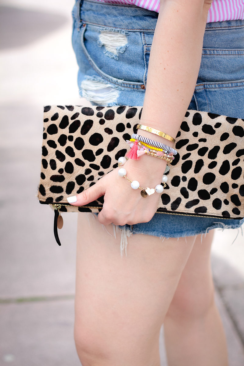 Miami fashion blogger Stephanie Pernas styles a Clare V leopard foldover clutch with jean shorts for summer