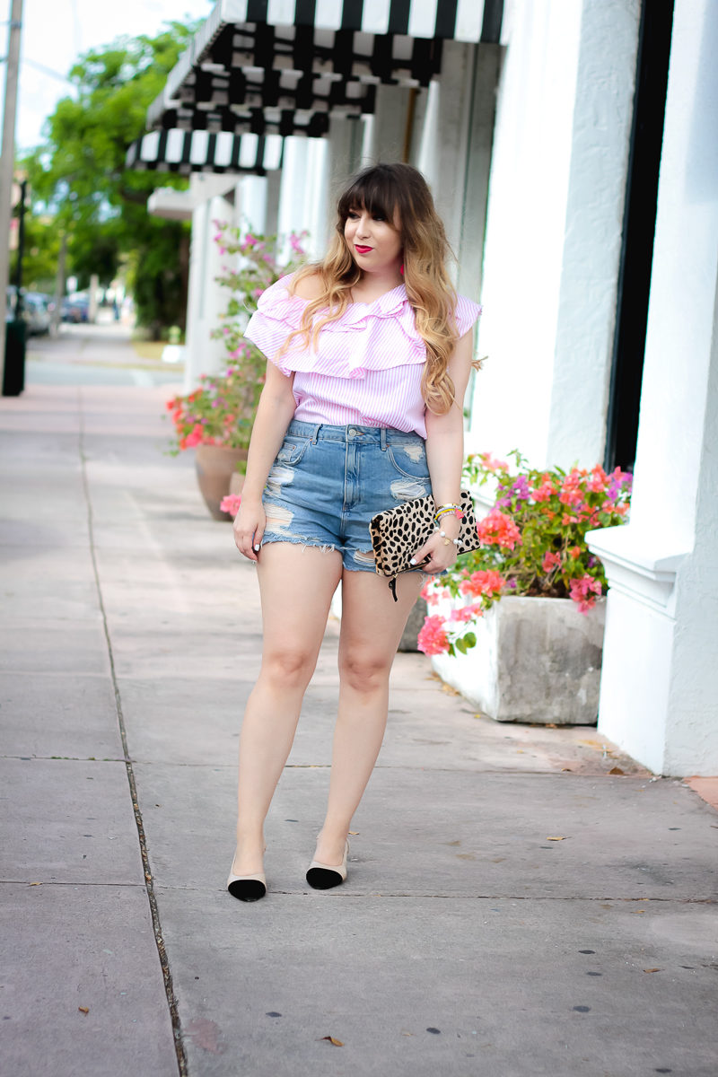 Miami fashion blogger Stephanie Pernas wearing a pink stripe one shoulder top and jean shorts for a casual summer outfit idea
