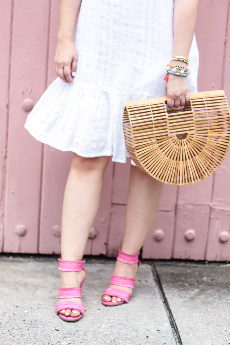 Miami fashion blogger Stephanie Pernas wearing a white dress and hot pink heels with a bamboo bag