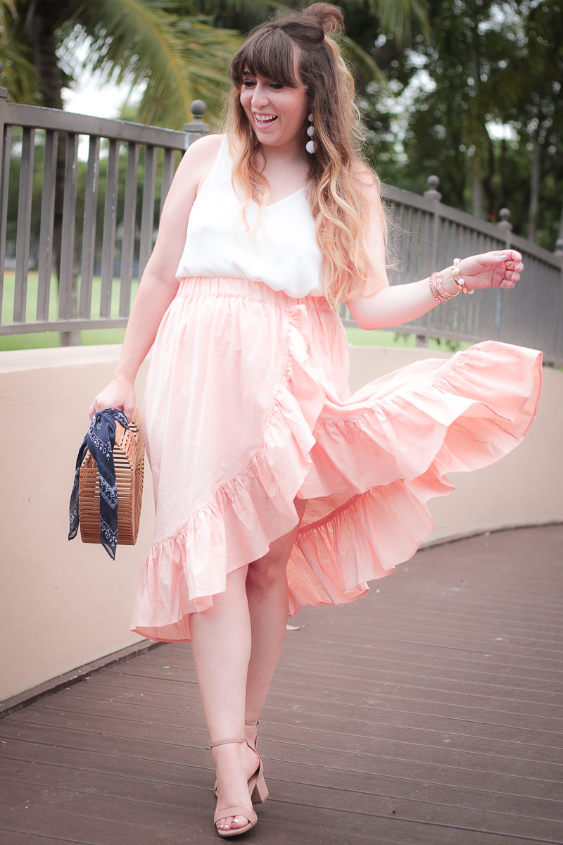 Fashion blogger Stephanie Pernas of A Sparkle Factor styles a pink wrap skirt and camisole
