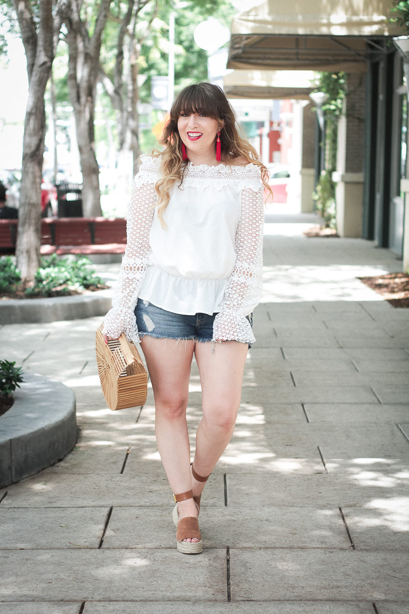 Miami fashion blogger Stephanie Pernas styles a white lace off the shoulder top and jean shorts for summer