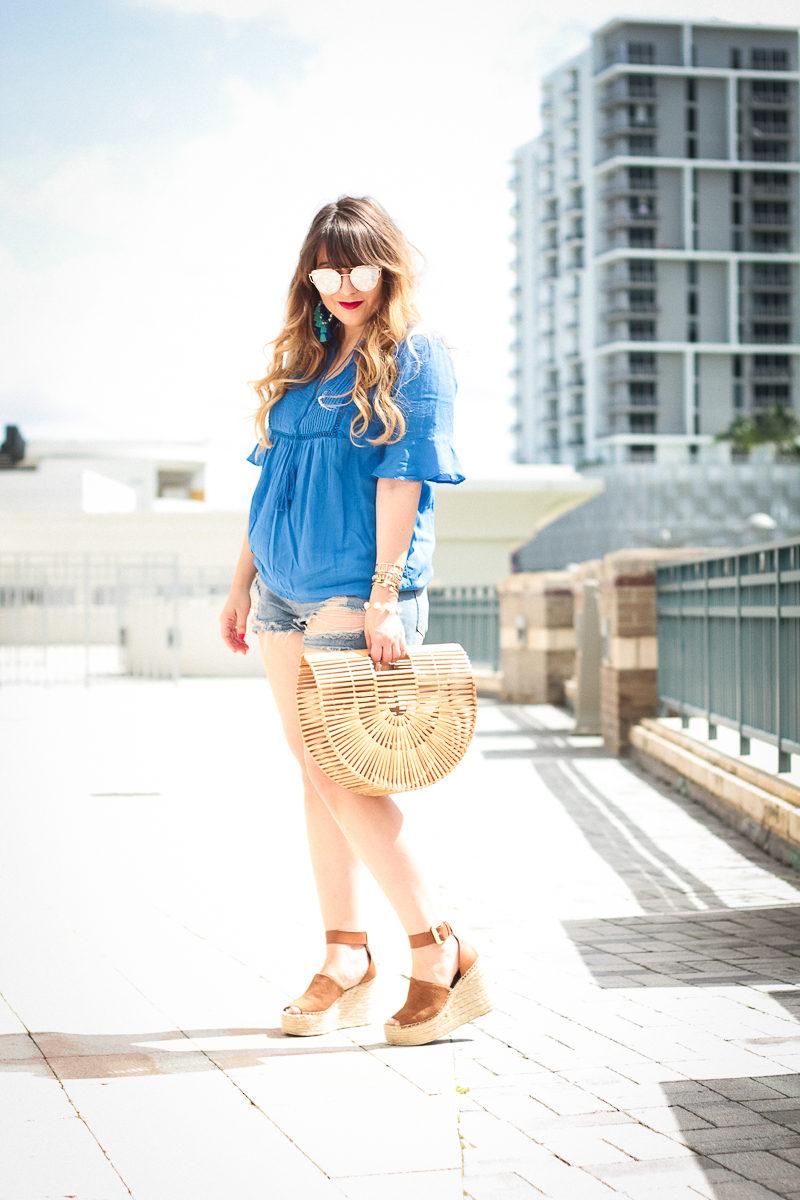 Miami fashion blogger Stephanie Pernas wearing a pin tuck swing top and denim cutoffs