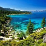 Breathtaking Lake Tahoe crystal clear water surrounded by a rocky shoreline and trees.