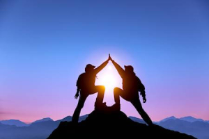 The Silhouette of two men with success gesture standing on the top of mountain