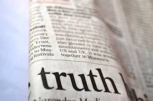 The Truth printed in large, bold headline in a folded newspaper