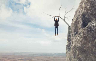 Picture of a man hanging from a weak branch above a canyon. Narrow Obamacare plans can leave you hanging.