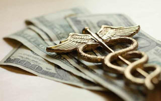 Medical symbol atop large denomination US currency. Free market healthcare shopping drives down consumer costs!
