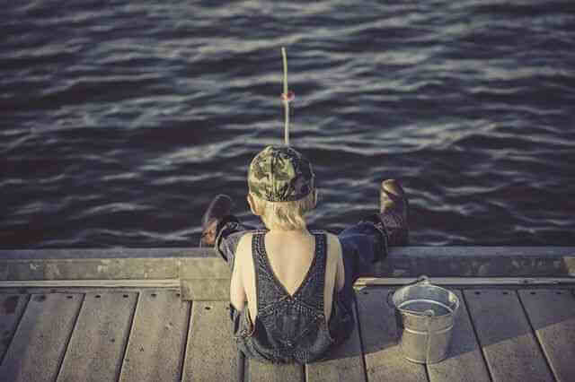 Small boy fishing off of a pier. This mere child is more competitive, principled, and worthy of edifying in respects to his fishing prowess than the aforementioned losers