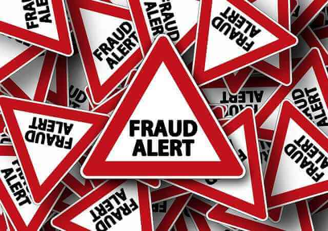 Triangular 'FRAUD ALERT' signs piled up to fill up image. Fraud Alert! Beware the healthcare scams during 'open enrollment!'
