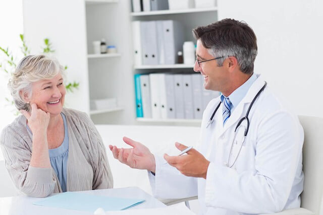 A doctor, cordial, speaking with a female patient. Patient communication is important? Can this really be a new revelation?
