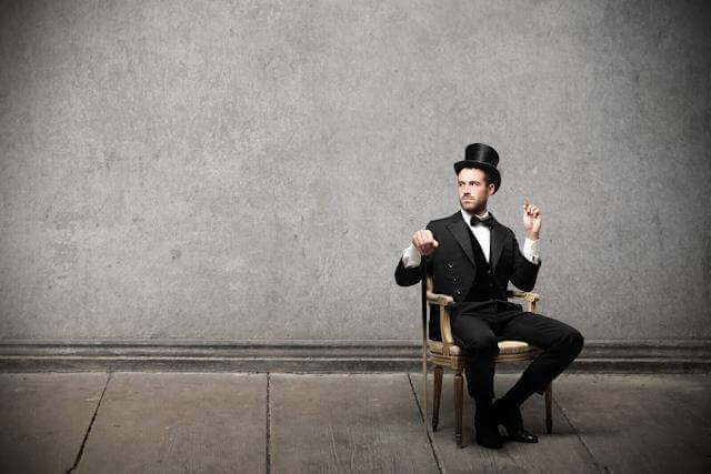 A magician with a top hat sitting on a chair placed on a barren stage. A magician act revealed: demystifying healthcare