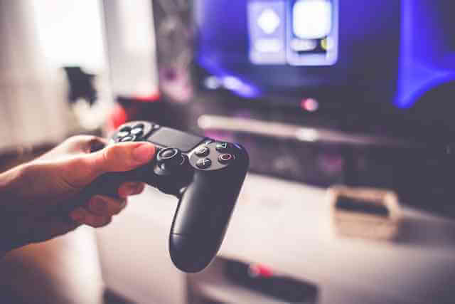 Video game controller being held with a television screen in the distance. Healthcare meet video games. Whether it be you or your video game character or avatar...you BETTER get good at overcoming and avoiding dangers and obstacles!